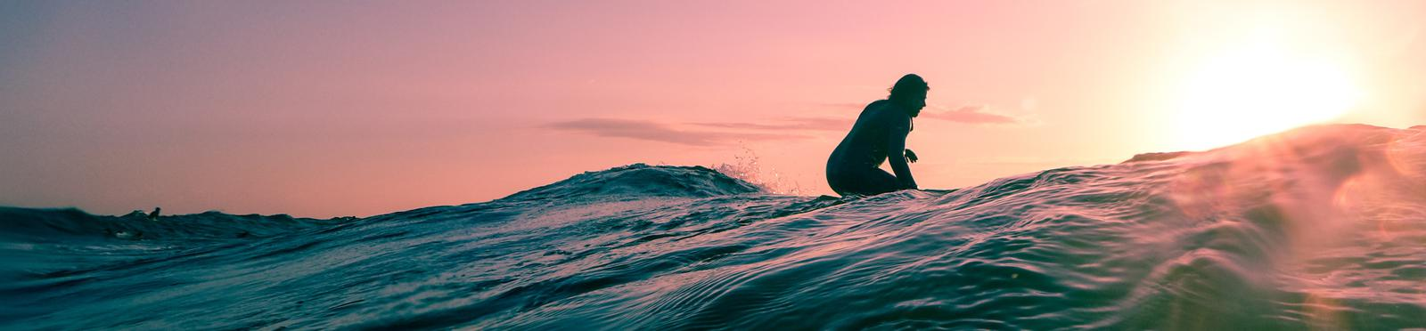 Man sitting on his board on the wave with a perfect pink sky