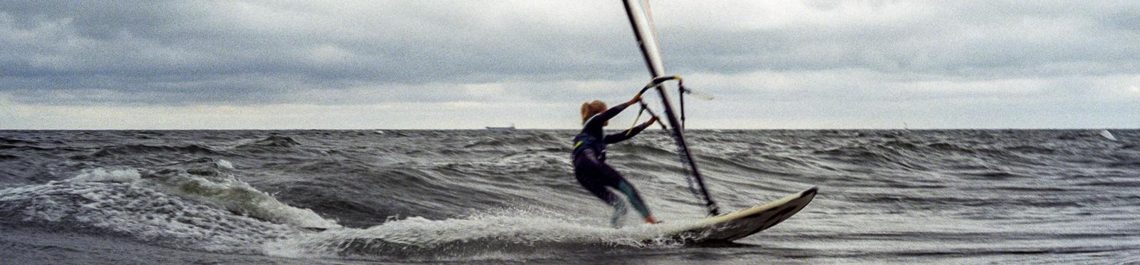 Girl on the windsurf in the middle of the sea.